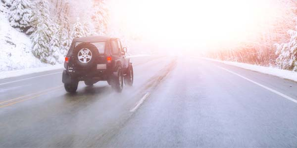 Jeep driving down winter roadway.