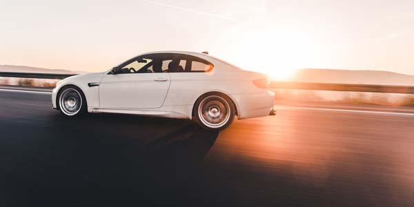 Luxury car on road during sunset