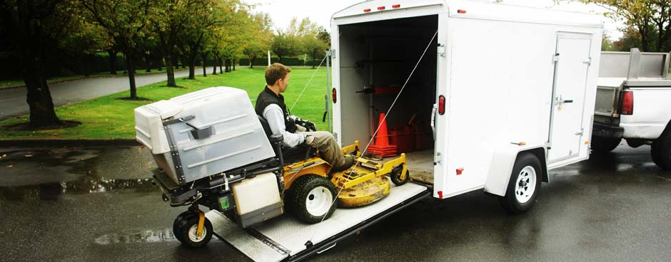 A landscape worker drive a riding lawnmower into a trailer.