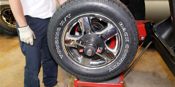 A tire and wheel set mounted on a tire balancing machine.