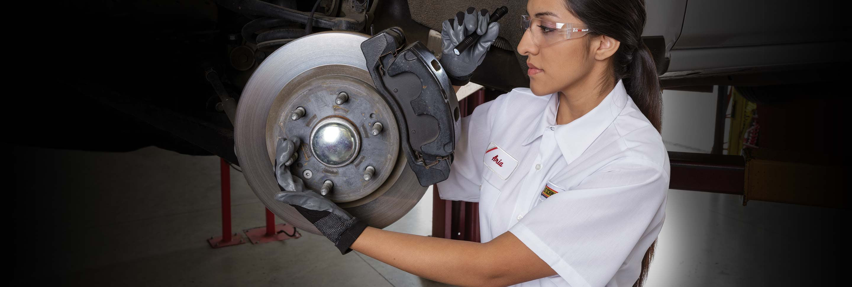 A Les Schwab technician inspecting a vehicle's brakes with a flashlight and protective glasses