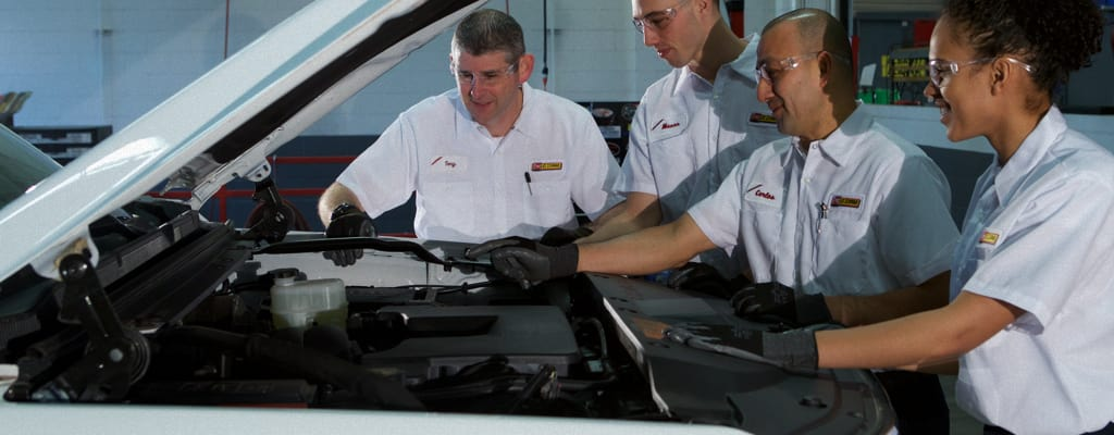 Four Les Schwab Employees Working Together On A Vehicle