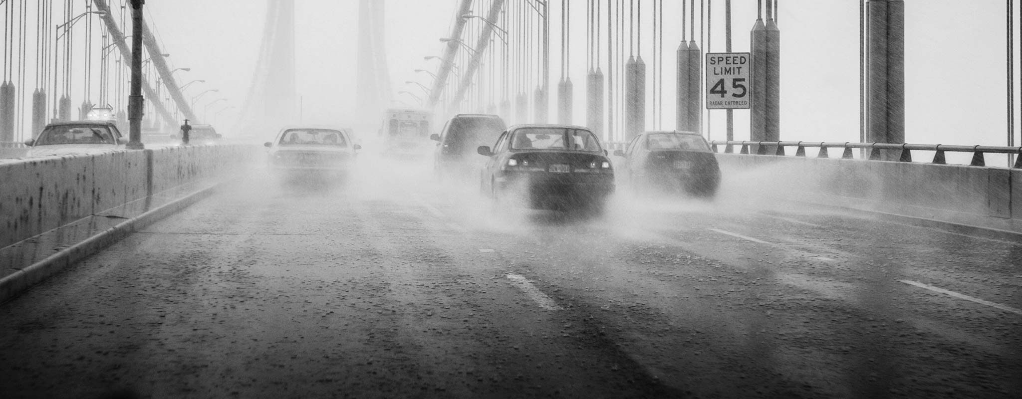 Cars on a wet rainy bridge.