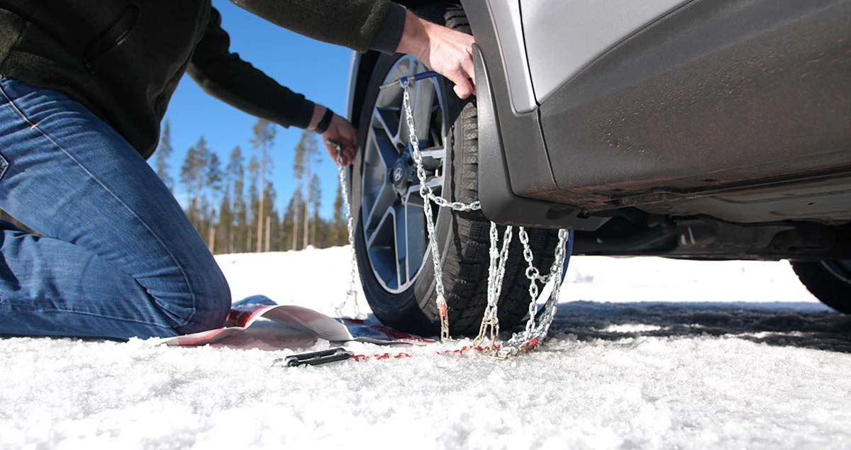 Man pulling tire chain up around tire.