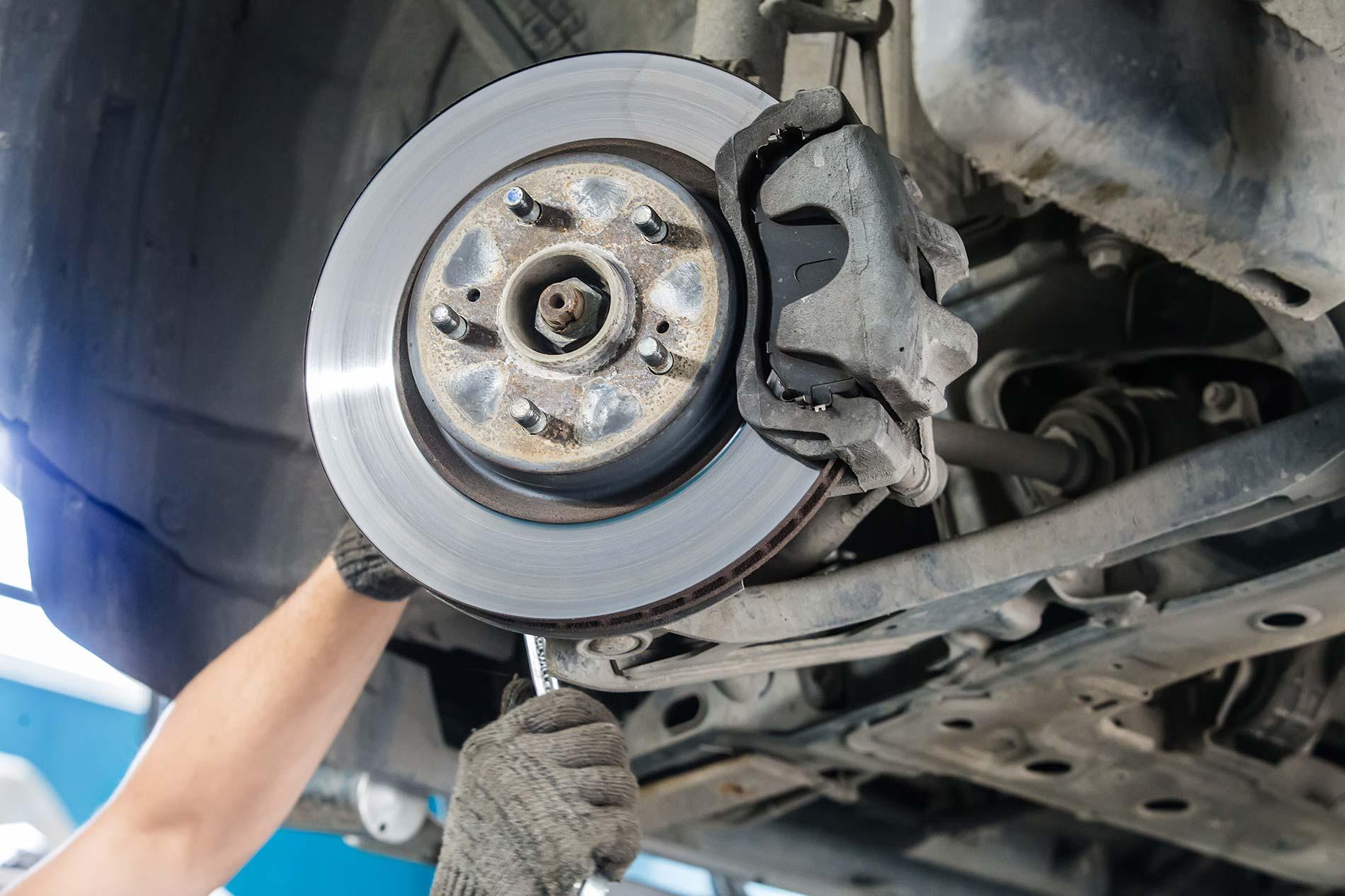 Technician adjusting disc brake on car