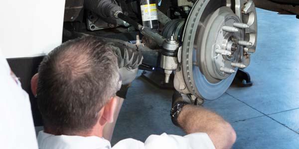 A Les Schwab technician points out a tire rod.