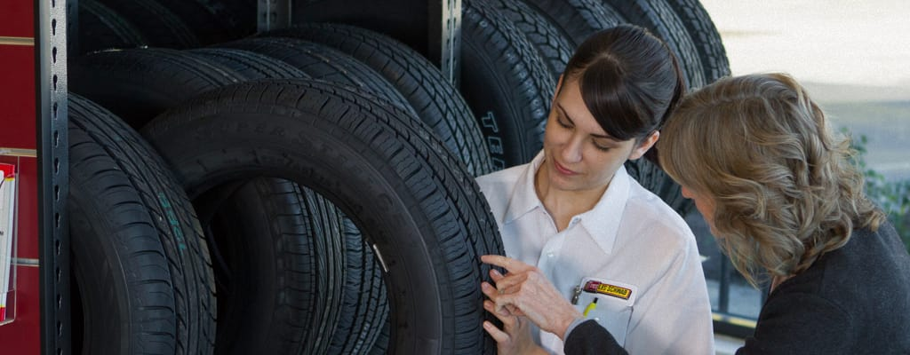 A wide shot of an employee showing tires to a female customer.