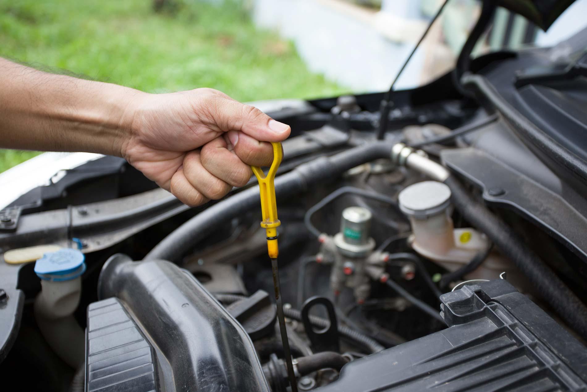 Person checking oil in car