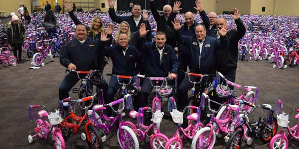 Les Schwab employees in a room full of children's bikes that they helped assemble.